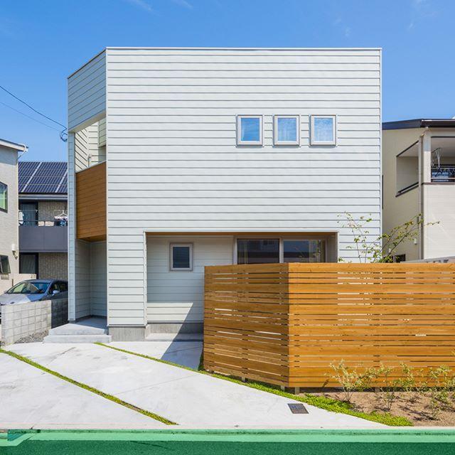 グレーのガルバリウム鋼板を横張りにし 2階の3連窓でシンプルな外観