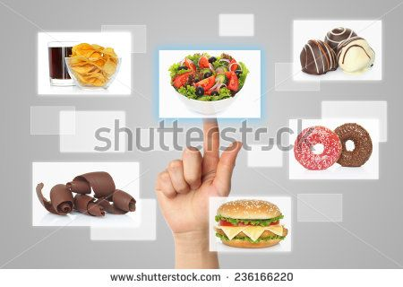 Woman hand uses touch screen interface with food on grey background
