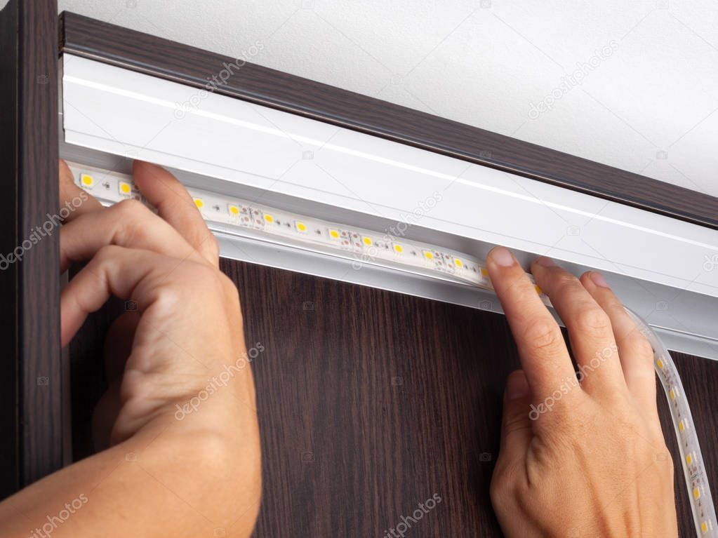 Electrician hands install LED strip lighting in the niche