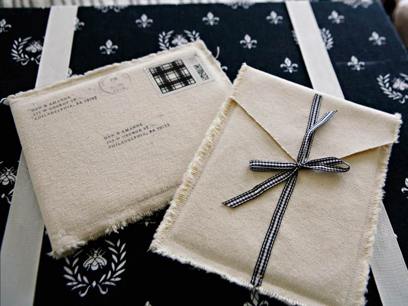 I dont know if the Post Office will like you for this one, but these invitations have been wrapped in hand sewn canvas bags.  The addresses and stamp have been printed onto iron on-fabric transfer paper (the invitations were printed on real wood!)