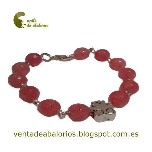 Pulsera de cadena con eslabones y piedras semipreciosas en color rojo. También se ha añadido un abalorio oso. La peculiaridad de esta pulsera es que se le pueden añadir cualquier tipo de abalorio como llave, símbolo infinito.....