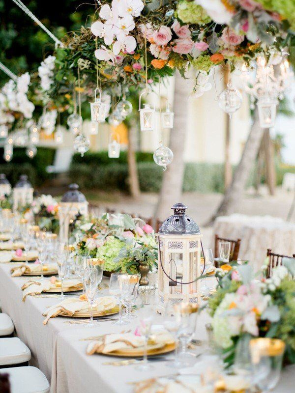 Garden wedding reception decor idea - hanging greenery with floating candles and lantern centerpieces {Destination Wedding Studio}