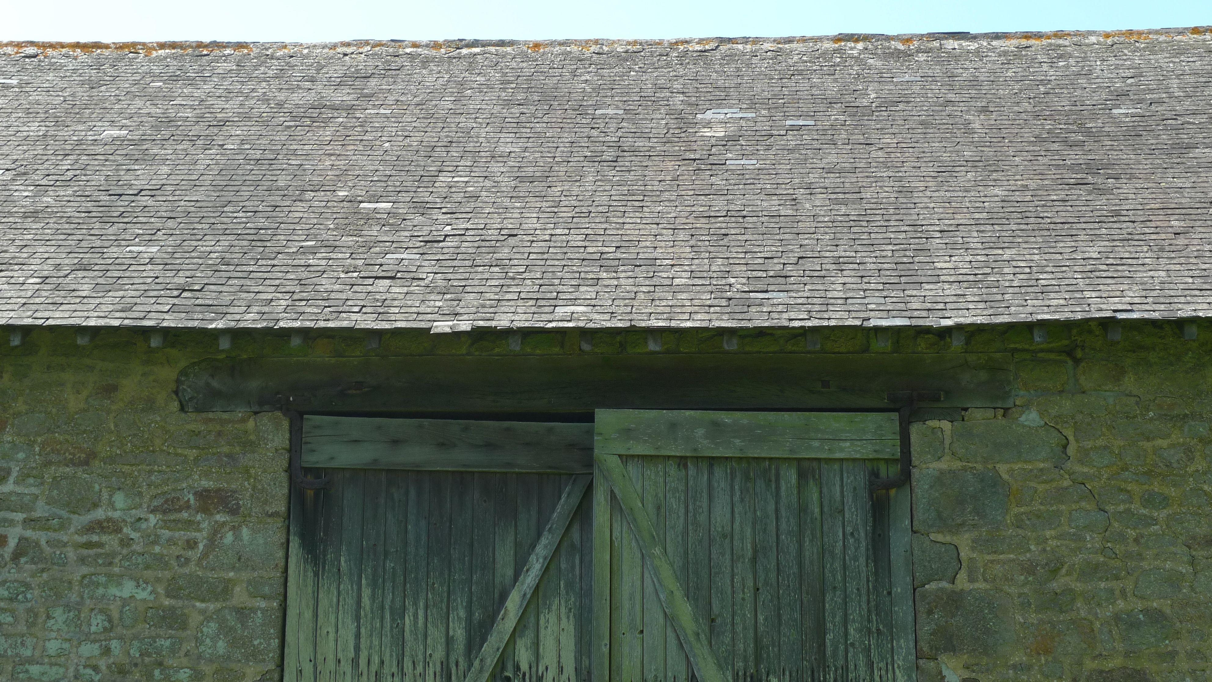 Slate tiled barn roof and oak doors in Pays de la Loire, France.