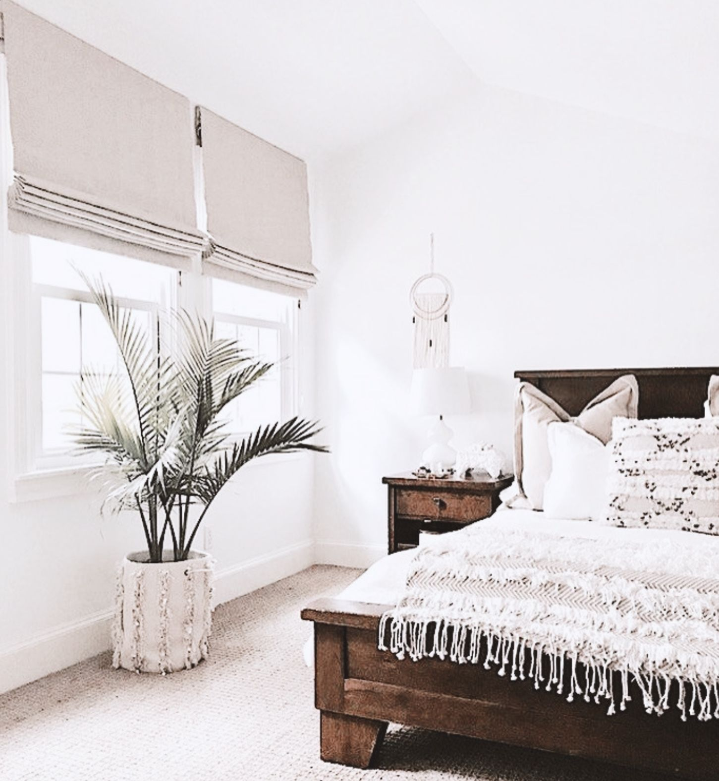 White Modern Bedroom With Fringe Duvet And Plant And Natural Wood