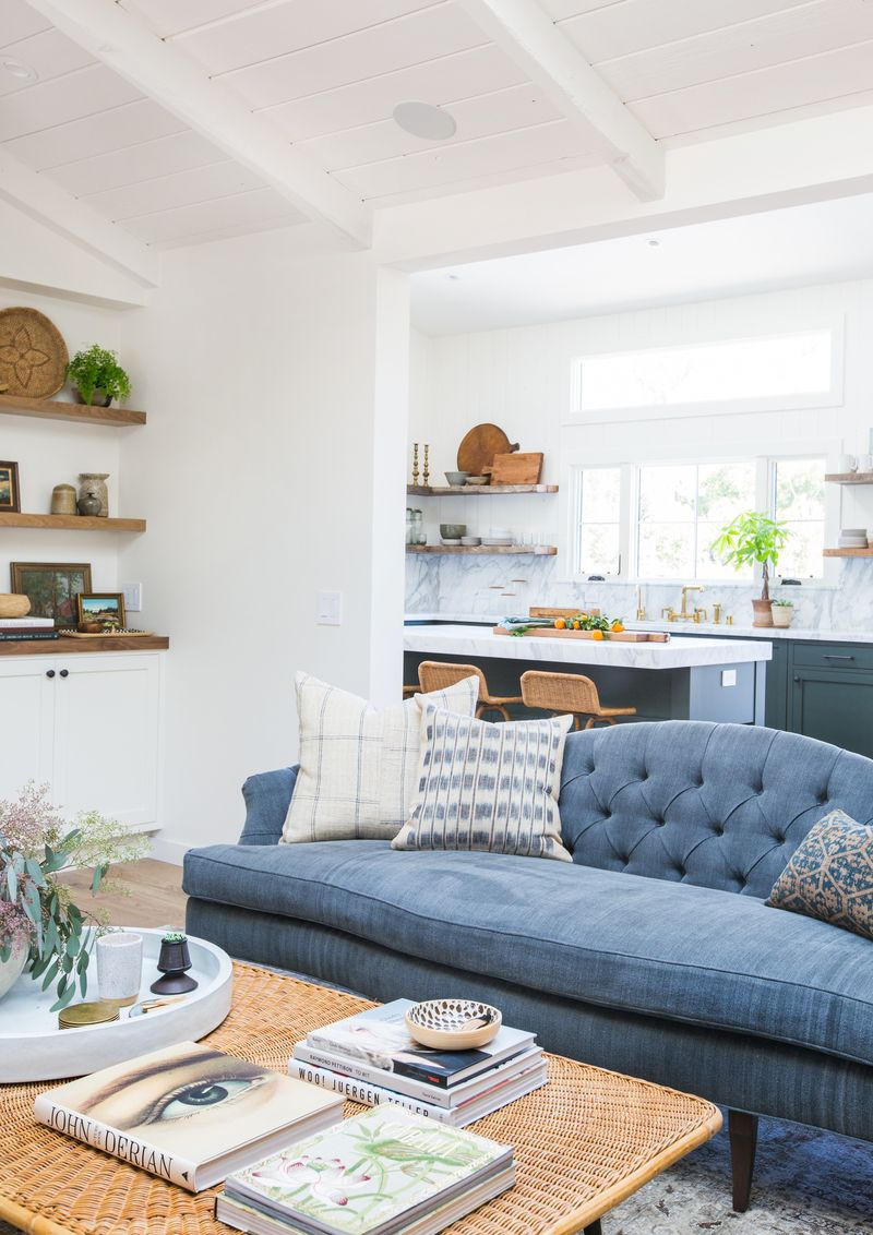 Blue tufted statement sofa in open floor plan living room design ...
