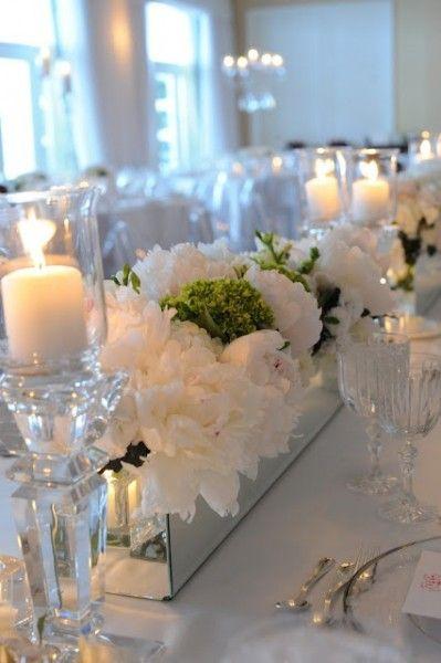 A mirrored rectangular vase filled with cream hydrangeas
