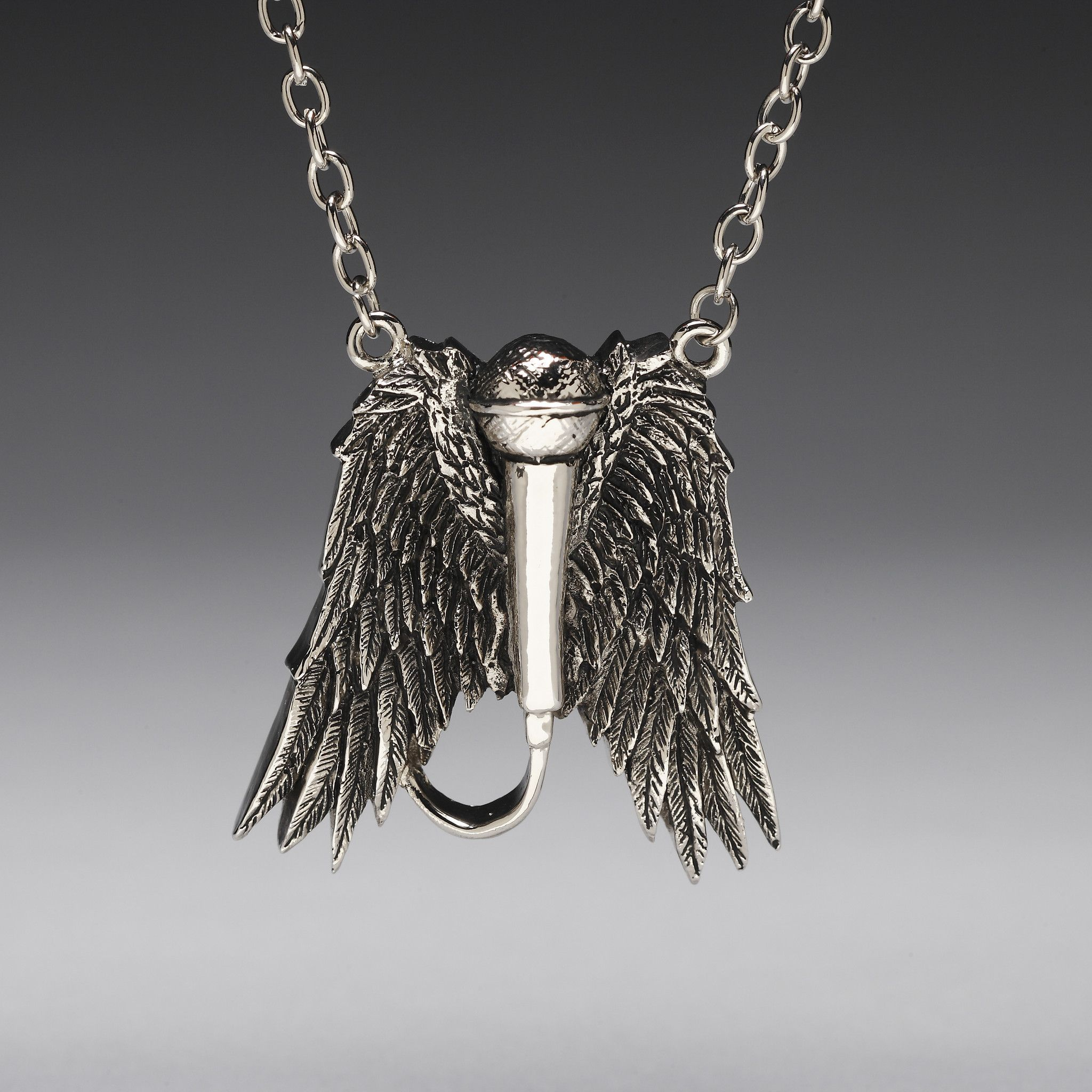 The Rock N' Roll Angel Pendant has very fine details with a semi-tarnished finish, and is featured on a larger-linked silver chain with a lobster clasp.