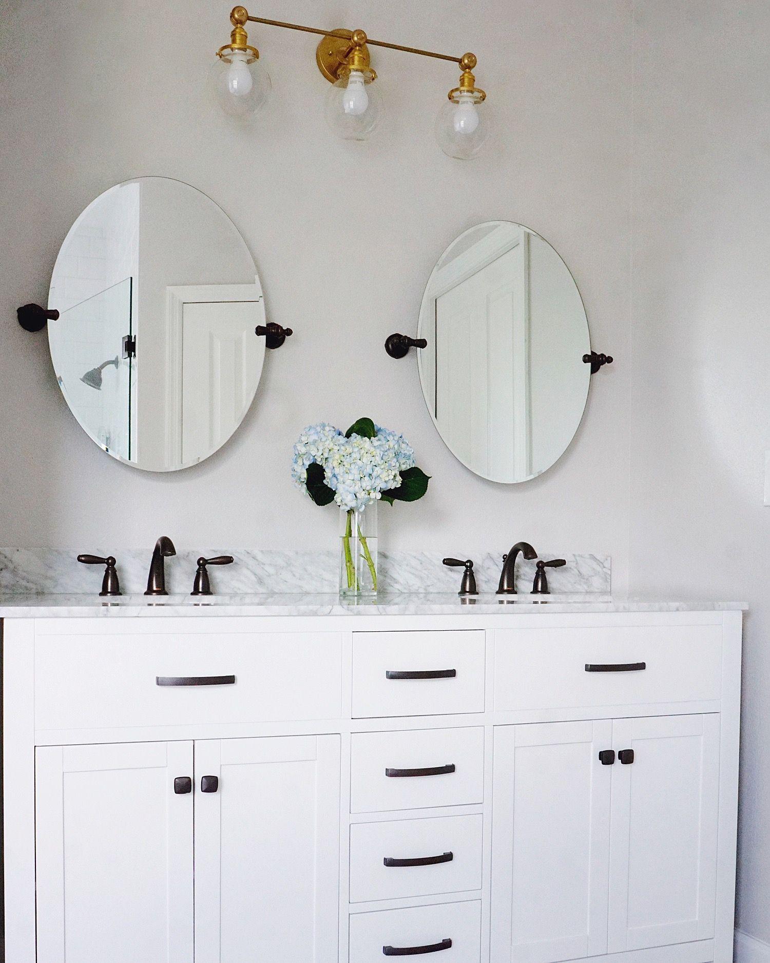 Oval mirror, brass vanity light, white marble vanity, oil