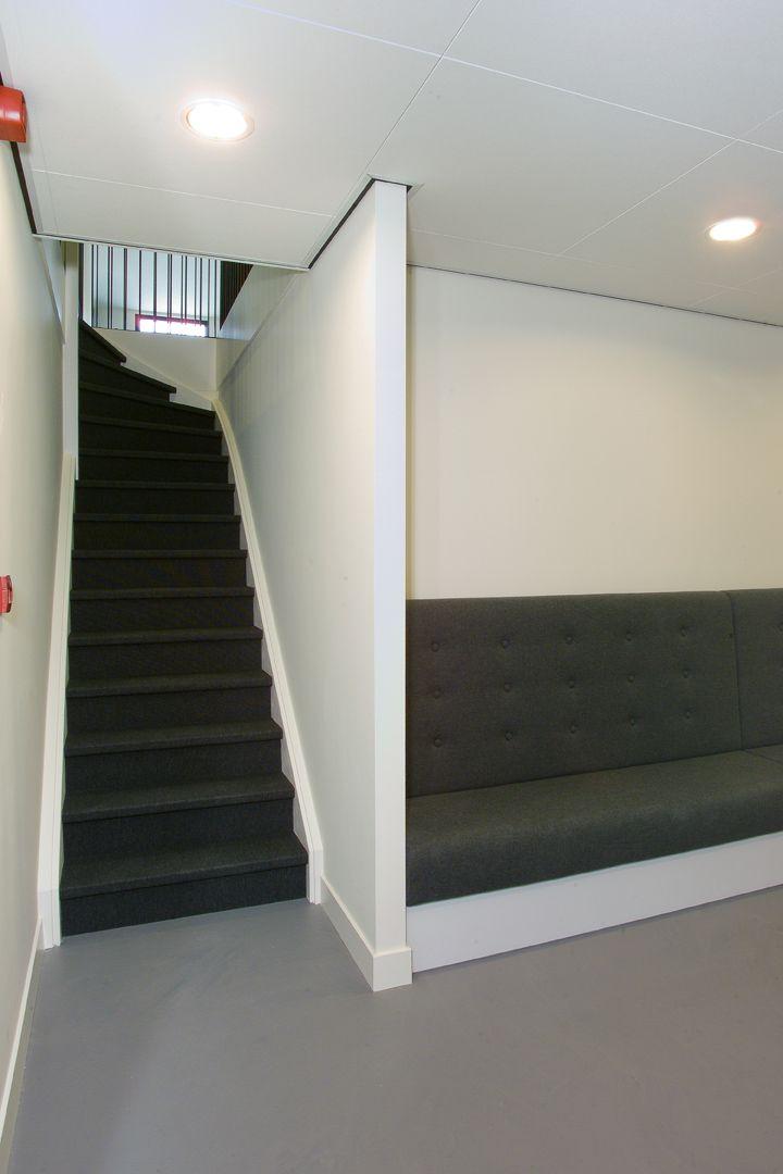 Houten trap bekleed met zwarte vloerbedekking grafisch ingedekt door gestuckte wanden slb - Entreehal met trap ...