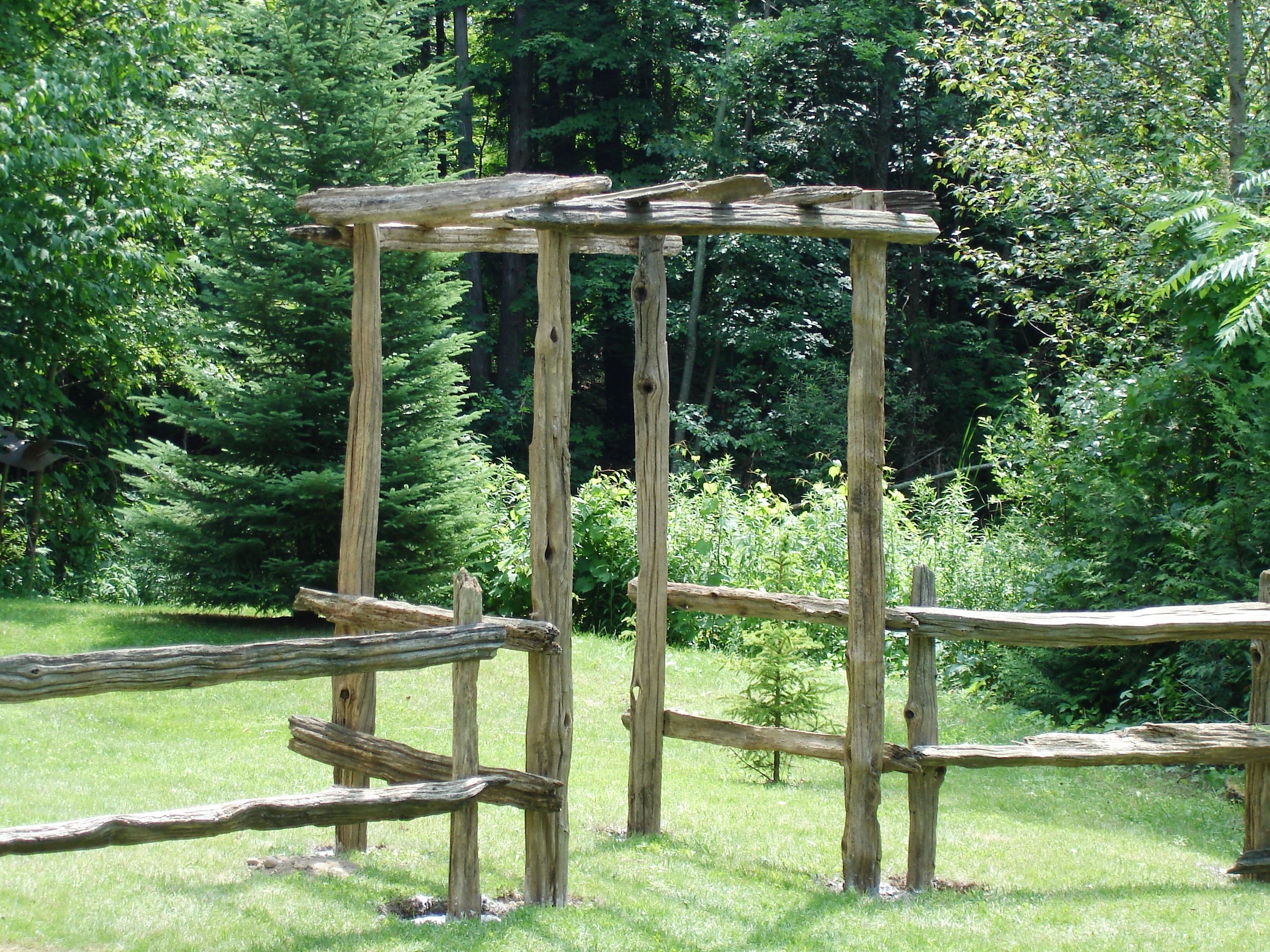 Old split cedar rail arbor and fence that we built at our