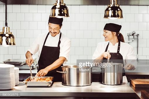 Stock Photo : Happy male and female chefs preparing food at kitchen counter