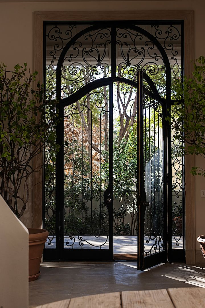 Wrought Iron And Glass Door Maintains A Garden Feel Between The