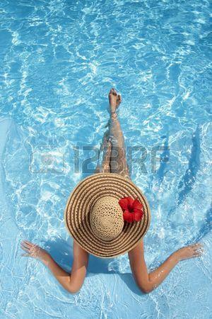 Mujer sentada en una piscina en un gran sombrero para el sol