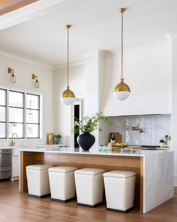 Hicks Pendants lights in white and gold illuminate a white and gray marble waterfall countertop island fitted with cream ottomans as stools. #waterfallcountertop