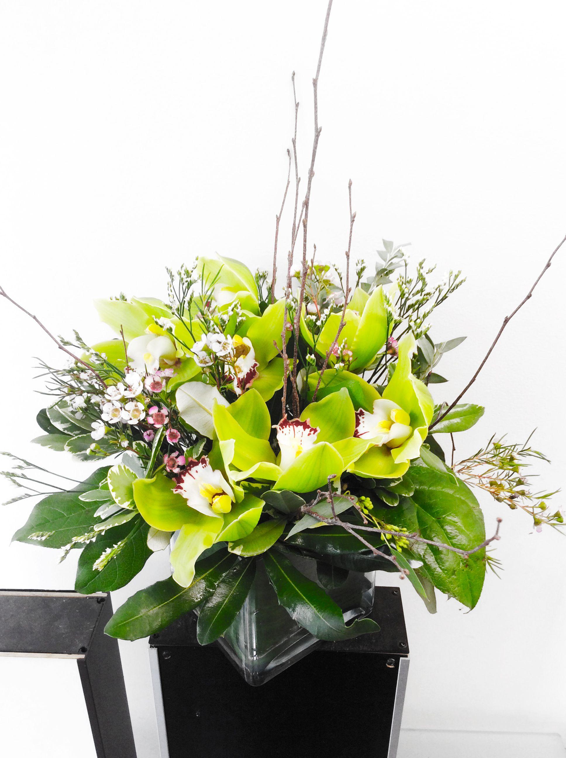 A Custom Floral Arrangement In A Square Vase Designed By