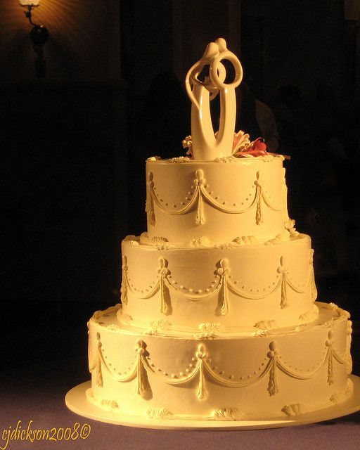 Wedding Cake With A Lladro Topper Taken From Outside Bay Window Bathed In Yellow Glow An Light