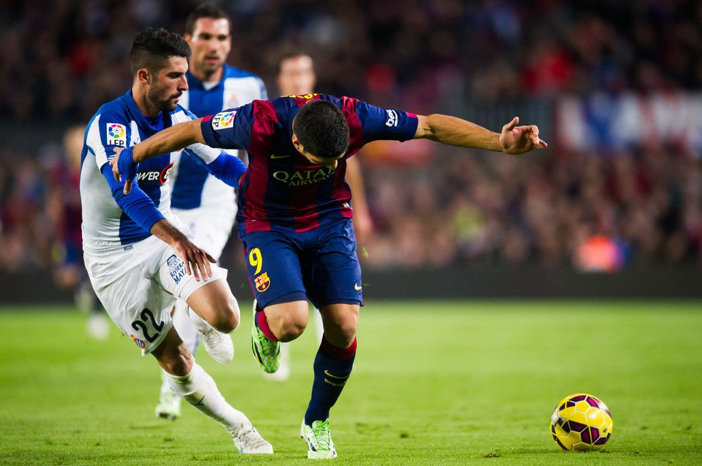 Alvaro Gonzalez (L) of RCD Espanyol and Luis Suarez of FC Barcelona fight for the ball during the La Liga match between FC Barcelona and RCD Espanyol at Camp Nou on December 7, 2014 in Barcelona, Catalonia.