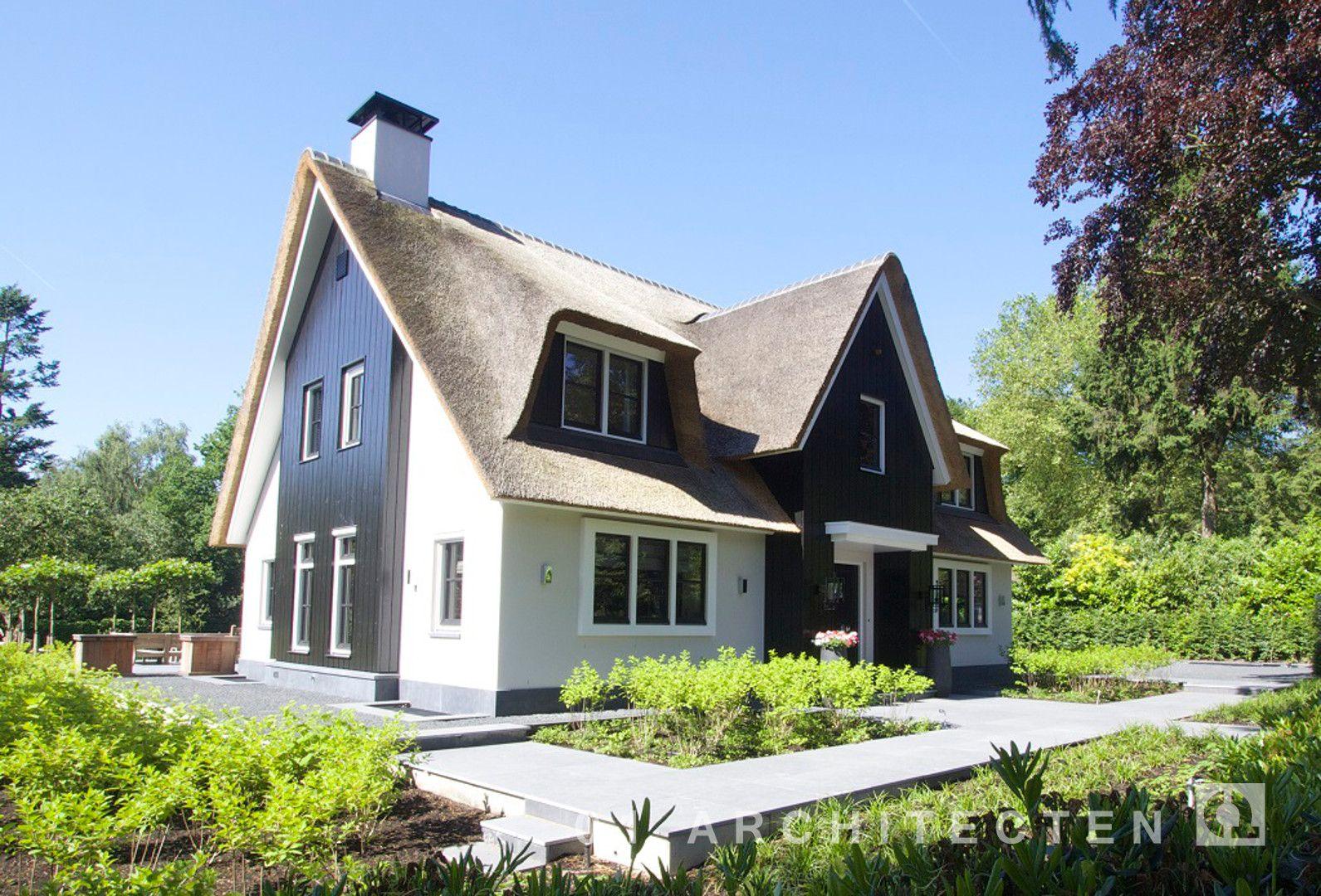 Witte rietgedekte villa met natuursteen trasraam houten accenten