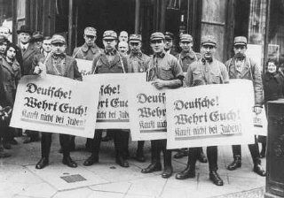 "During the anti-Jewish boycott, SA men carry banners which read ""Germans! Defend Yourselves! Do Not Buy From Jews!"" Berlin, Germ"