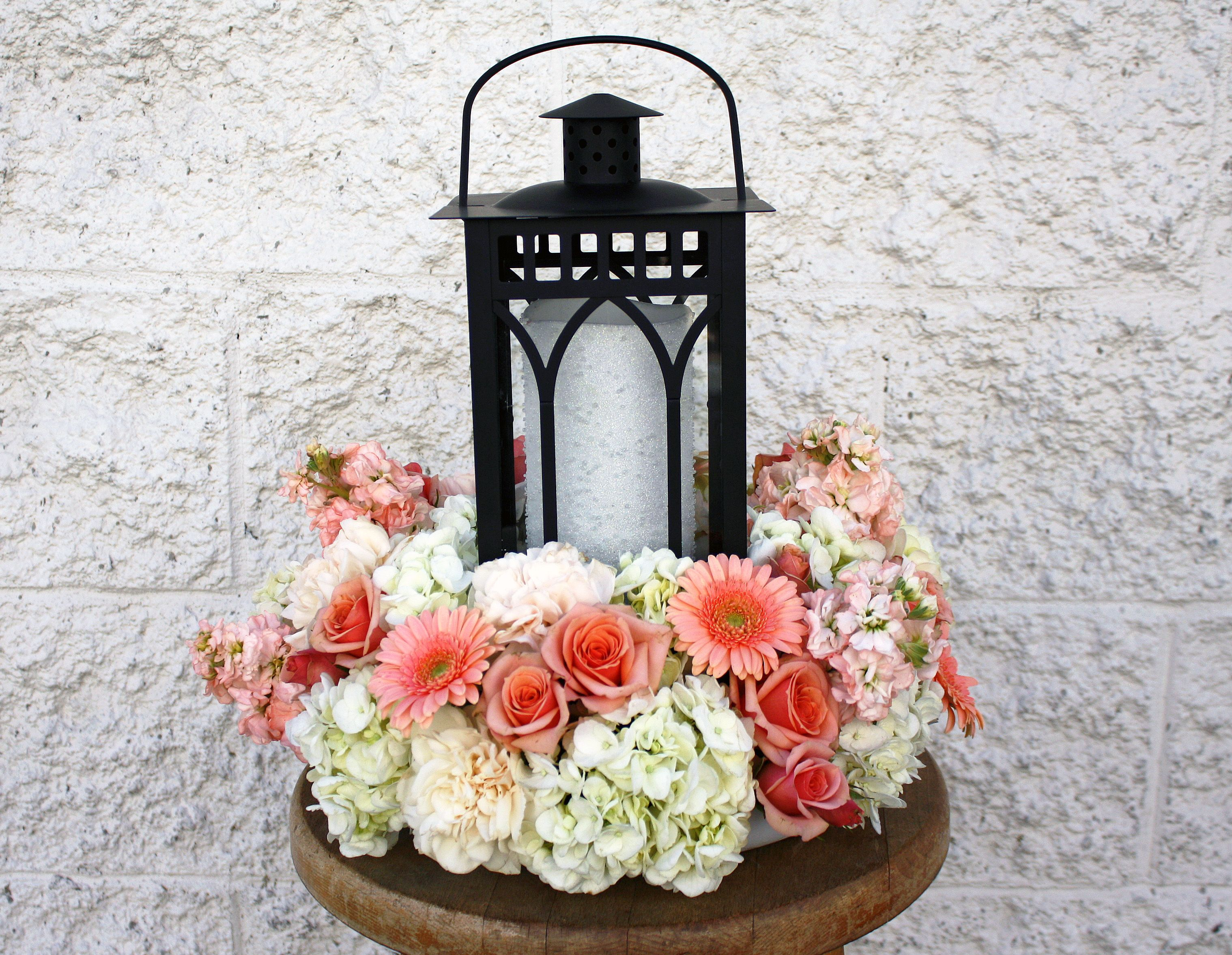 A beautiful lantern centerpiece with hydrangea, stock, roses and ...