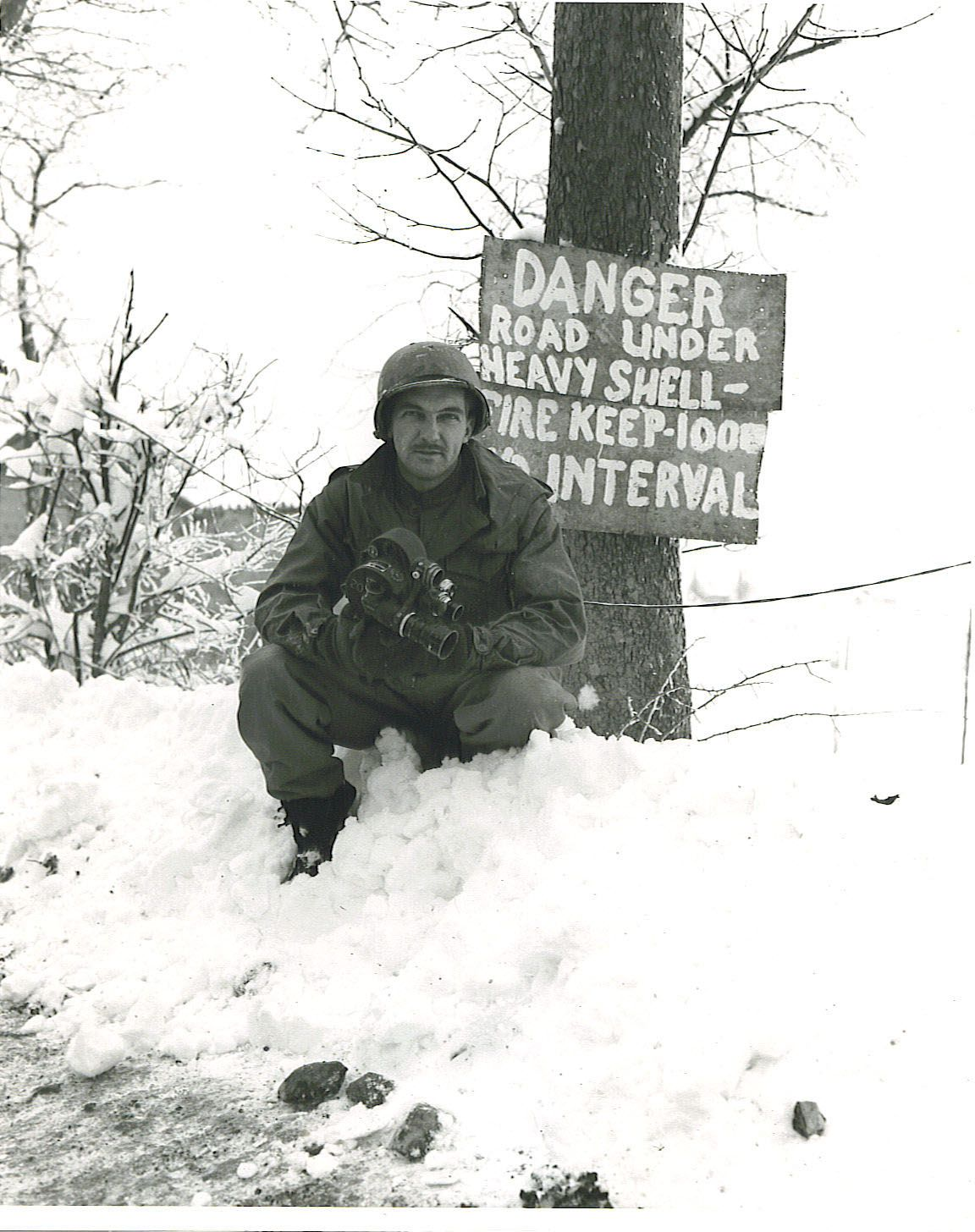 U.S. Army Signal Corps photographer Edmund Burke O'Connell, a motion picture photographer attached with the 196th Signal Photographic Company with his Bell & Howell 35mm Eyemo 71-Q motion picture camera during the Battle of the Bulge, Dec. 1944.