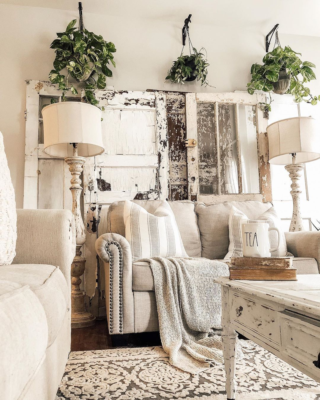 The Distressed Accents Paired With The Hanging Greenery Give This Space A Cozy Farmhouse Vibe That We Are Lo Farm House Living Room Home Living Room Home Decor #shabby #chic #decorating #ideas #living #room