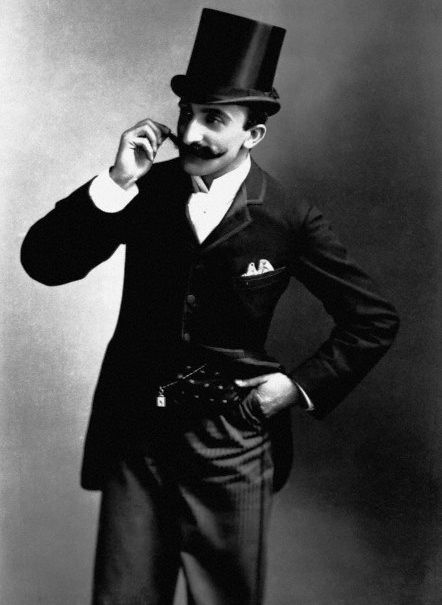 Man in top hat twirling his moustache. (ca. 1910s)
