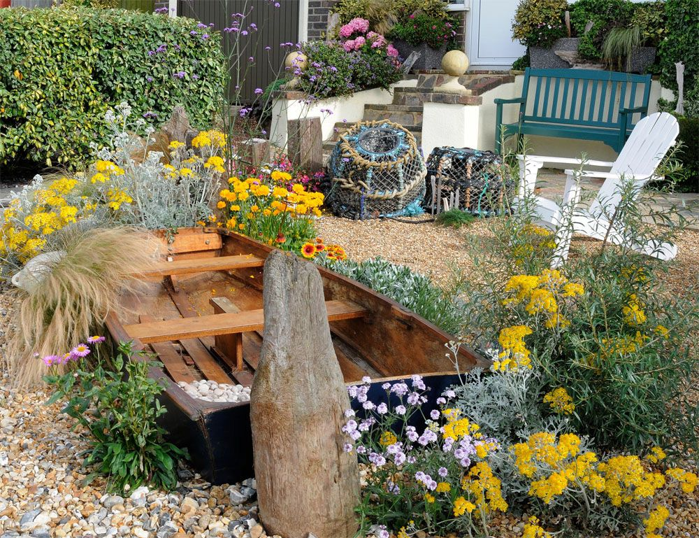 Boat Beached In Shingle And Flowers   Driftwood Garden By Geoff Stonebanks