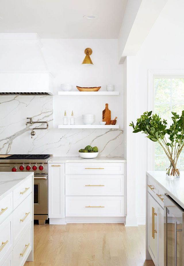 Gorgeous White Kitchen with Light Wood Flooring, Open Shelves, Brass Sconce and Hardware