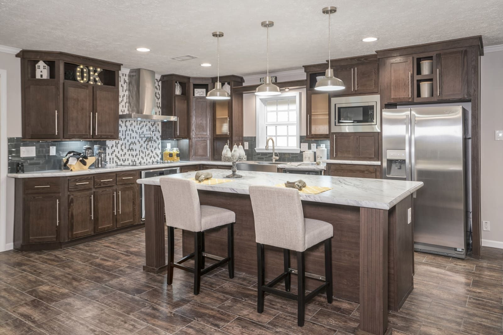 Kitchen with dark cabinets, wood floors, stainless steel ...