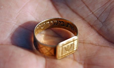 A golden wedding ring inscribed in Hebrew with the words Behold