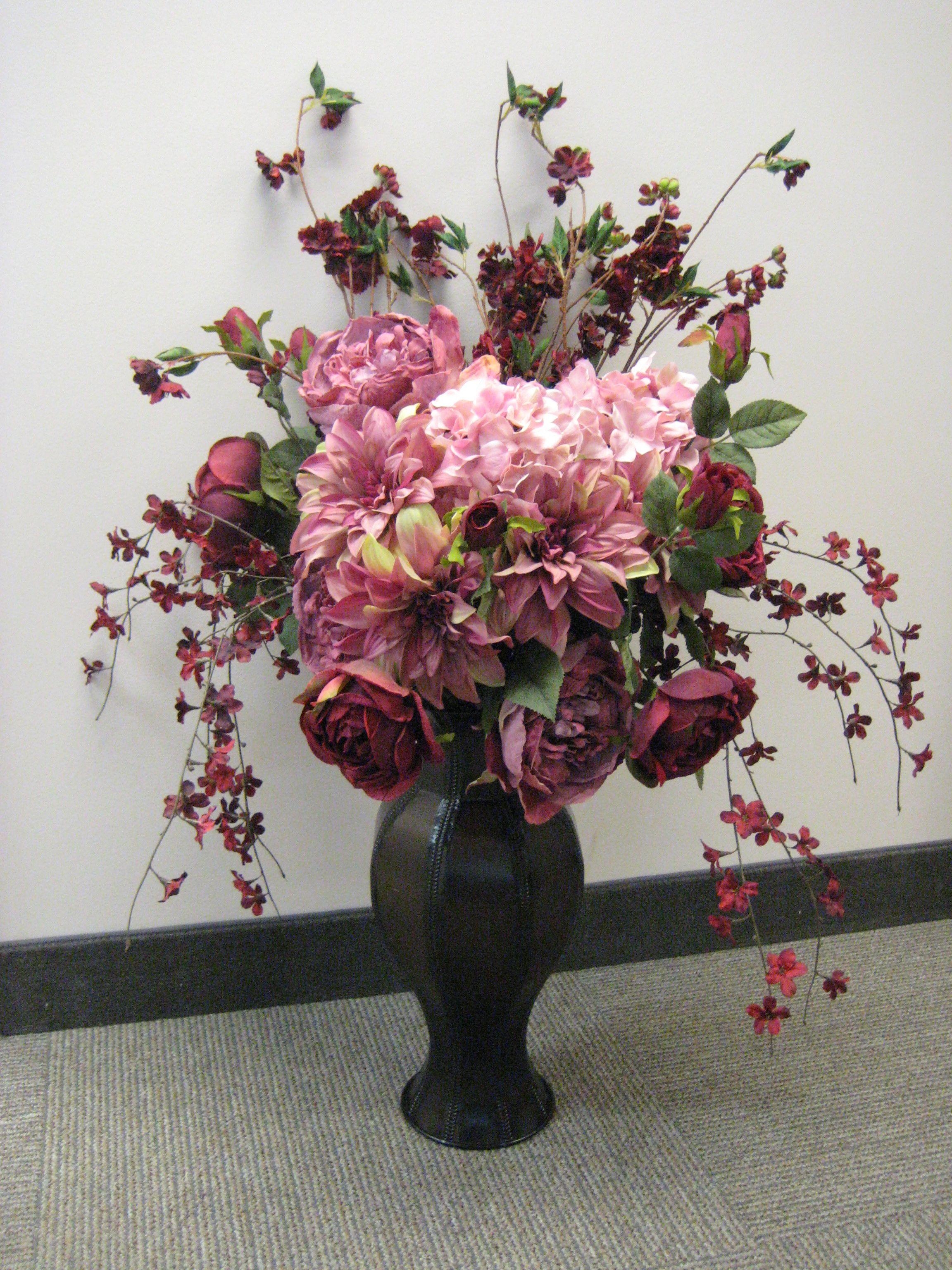 Beautiful arrangement of simple silk flowers in shades of pinkmauve beautiful arrangement of simple silk flowers in shades of pinkmauve overflowing out of dark mightylinksfo