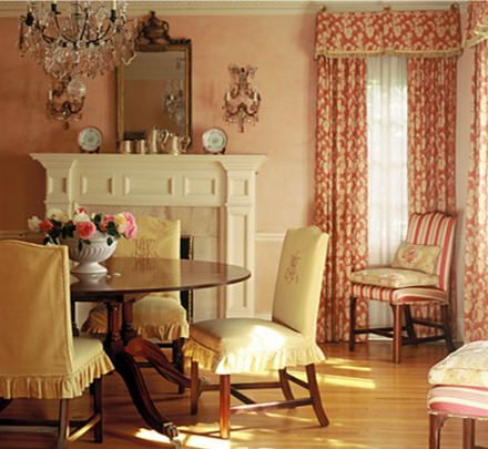 An English country dining room featuring monogrammed slip covers and sponged walls in a rosy peach shade. Thomas Callaway Associates