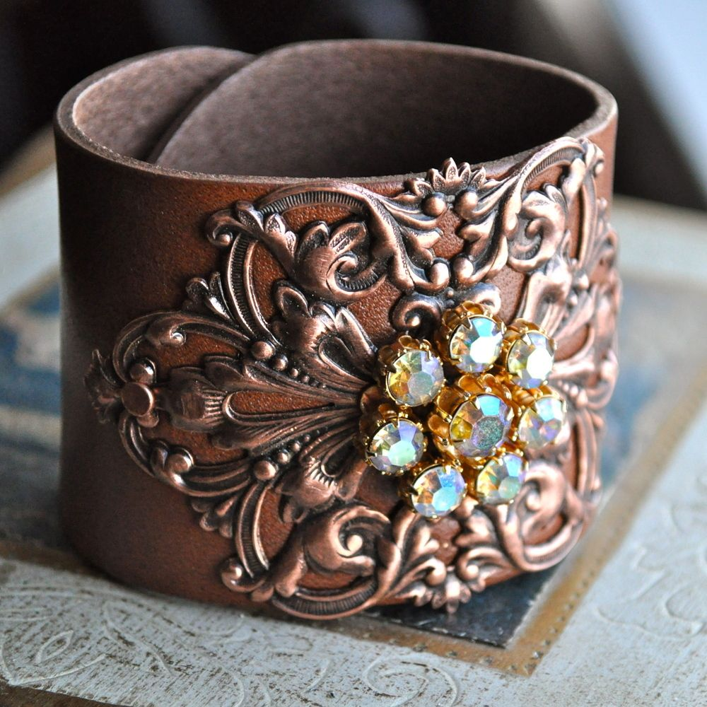 "Stunning adjustable brown leather cuff (2""), adorned with a copper antique stamping and a beautiful Weiss vintage rhinestone component.  This creation looks fantastic with jeans, boots and a simple tee!  Allow it to be ""the"" accessory.  The leather is firm, and will soften with wear.  One of my absolute favorites!"