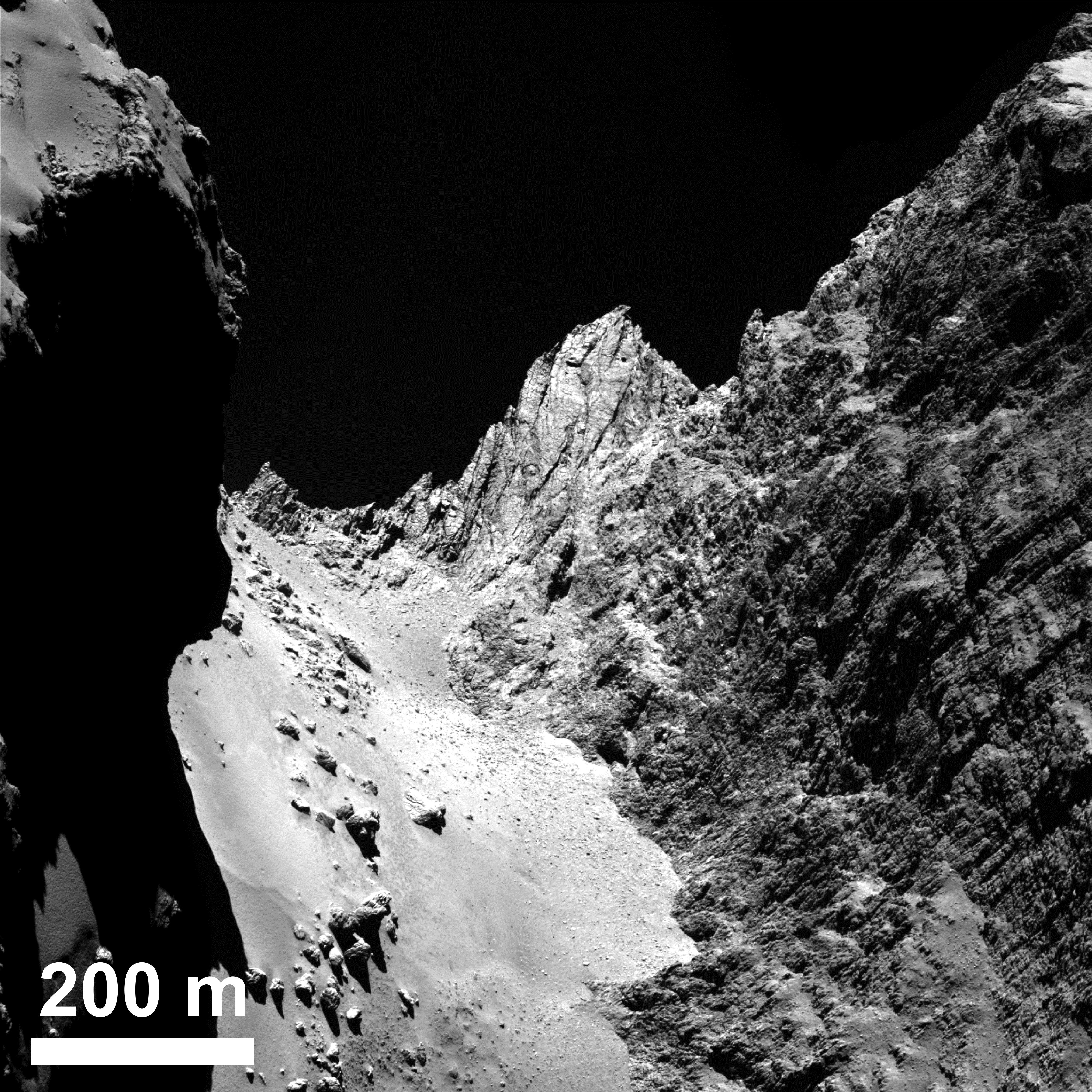 The boulder-strewn, smooth Hapi region in Comet 67P/Churyumov-Gerasimenko's neck, with the Hathor cliff face to the right.  Credits: ESA/Rosetta/MPS for OSIRIS Team MPS/UPD/LAM/IAA/SSO/INTA/UPM/DASP/IDA