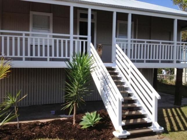 Simple and attractive porch railing. Crisp pale grey and white trim colour scheme. Stair treads with painted sides and oiled wood centre to conceal wear.
