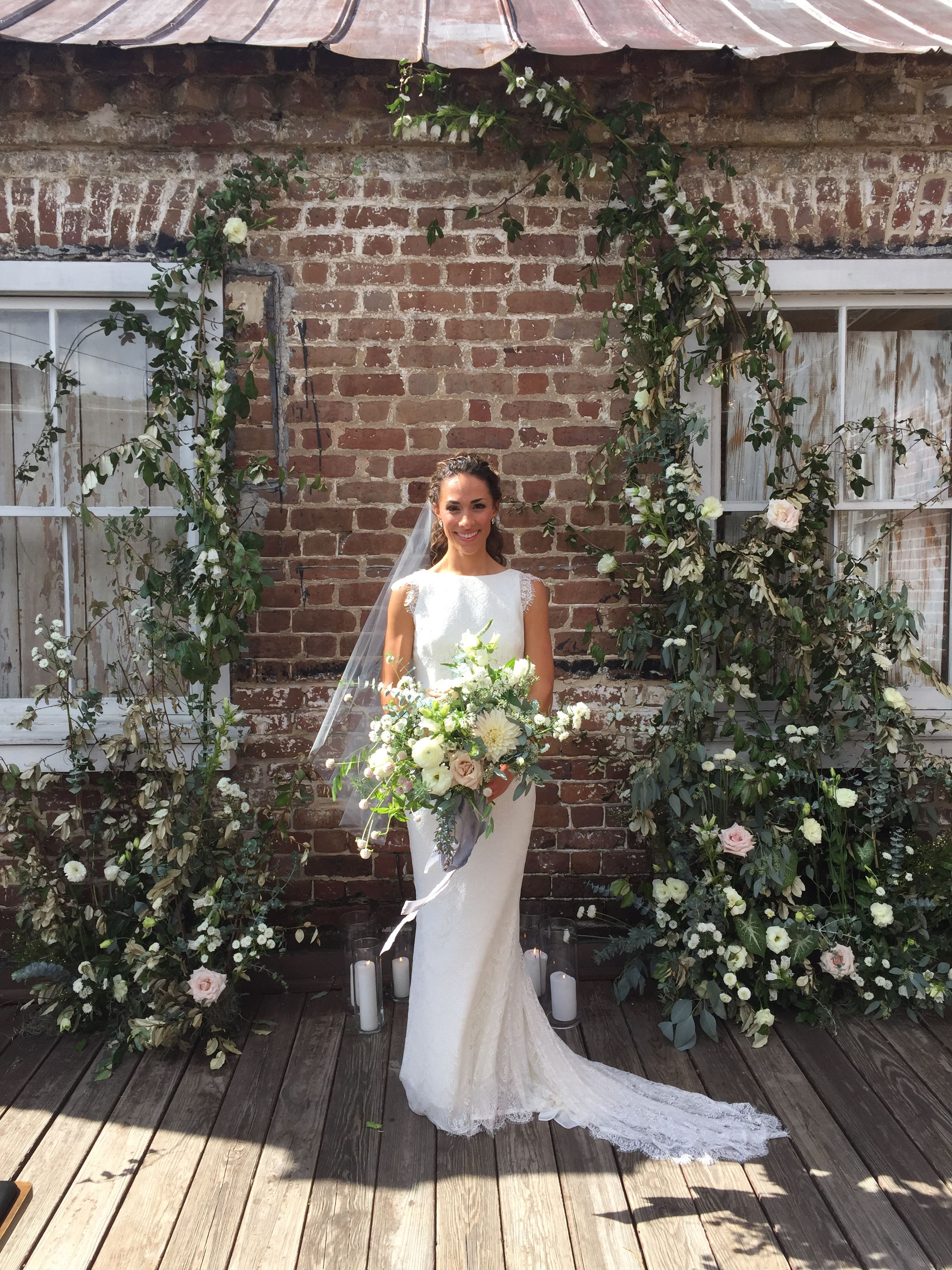 Greenery Arch Backdrop With White Flowers Against Brick Wall For Wedding Ceremony In Charleston Sc Wedding Ceremony Flowers Wedding Alters Brick Wall Backdrop