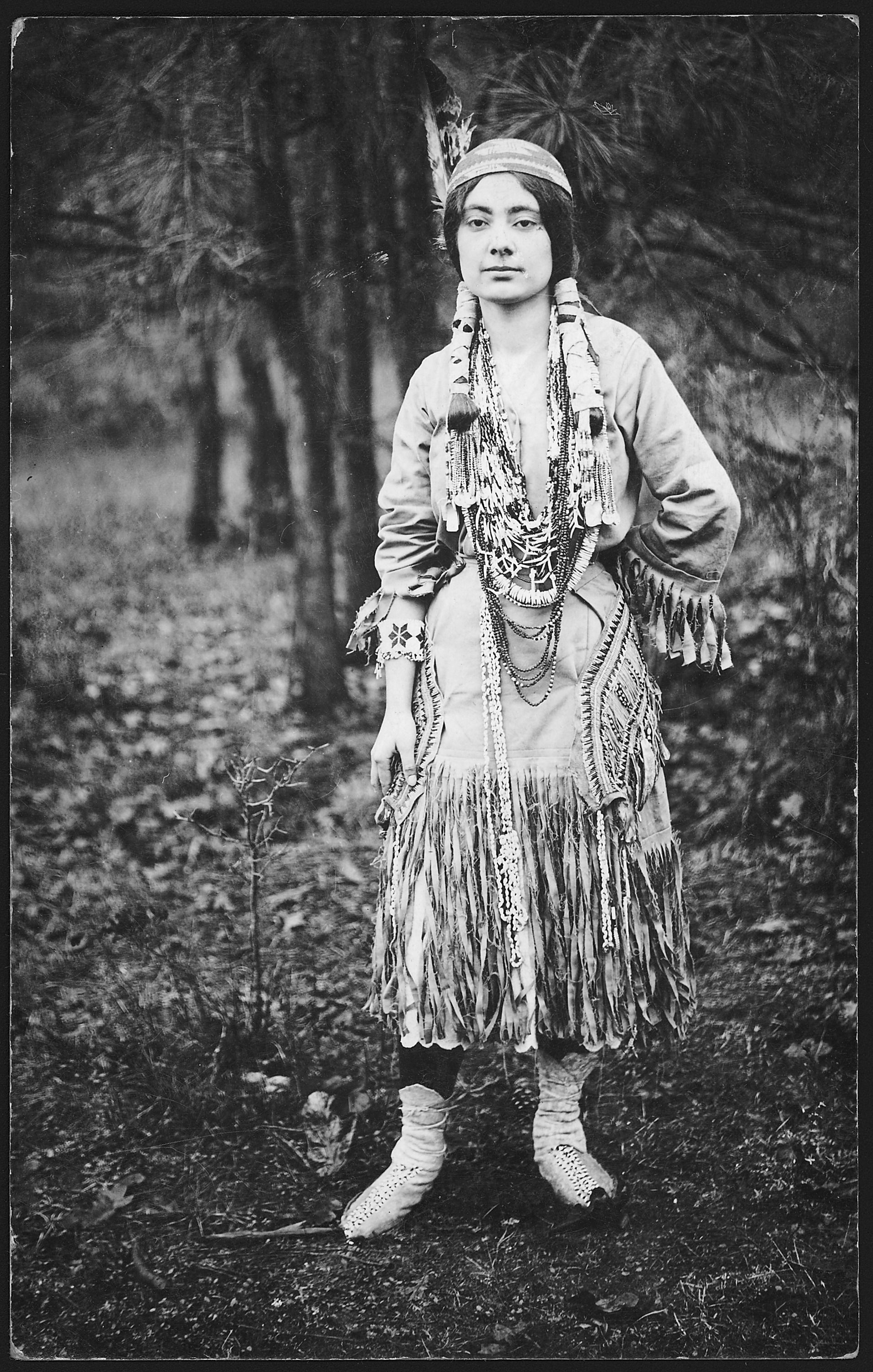 An old photograph of an Native American Maiden in Traditional Dress