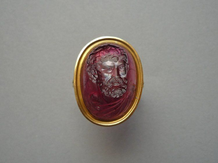 Intaglio; carbuncle; bust of bearded philosopher(?), three-quarters, wearing mantle; stone hollowed at back in oriental manner to increase transparency and brilliance; in gold ring.