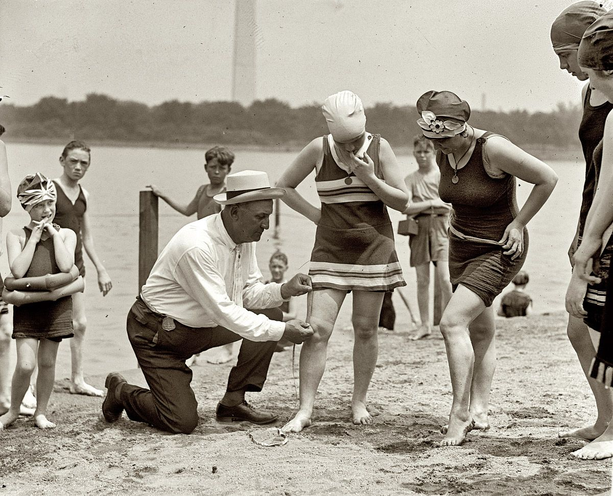 June 30, 1922. Washington policeman Bill Norton measuring the distance between knee and suit at the Tidal Basin bathing beach after Col. Sherrill, Superintendent of Public Buildings and Grounds, issued an order that suits not be over six inches above the knee. National Photo Co.
