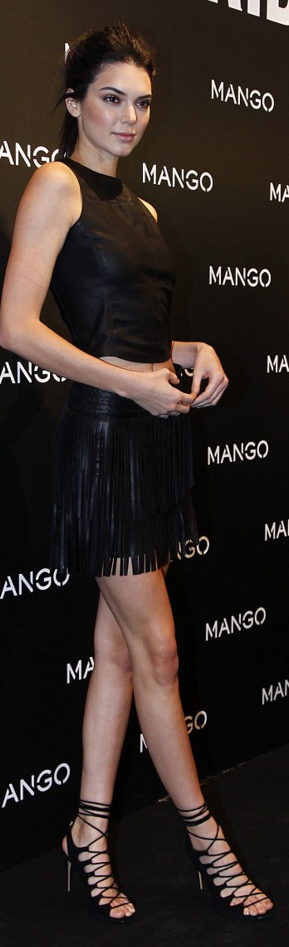 Who made  Kendall Jenner's black fringe skirt, leather top, and lace up sandals?