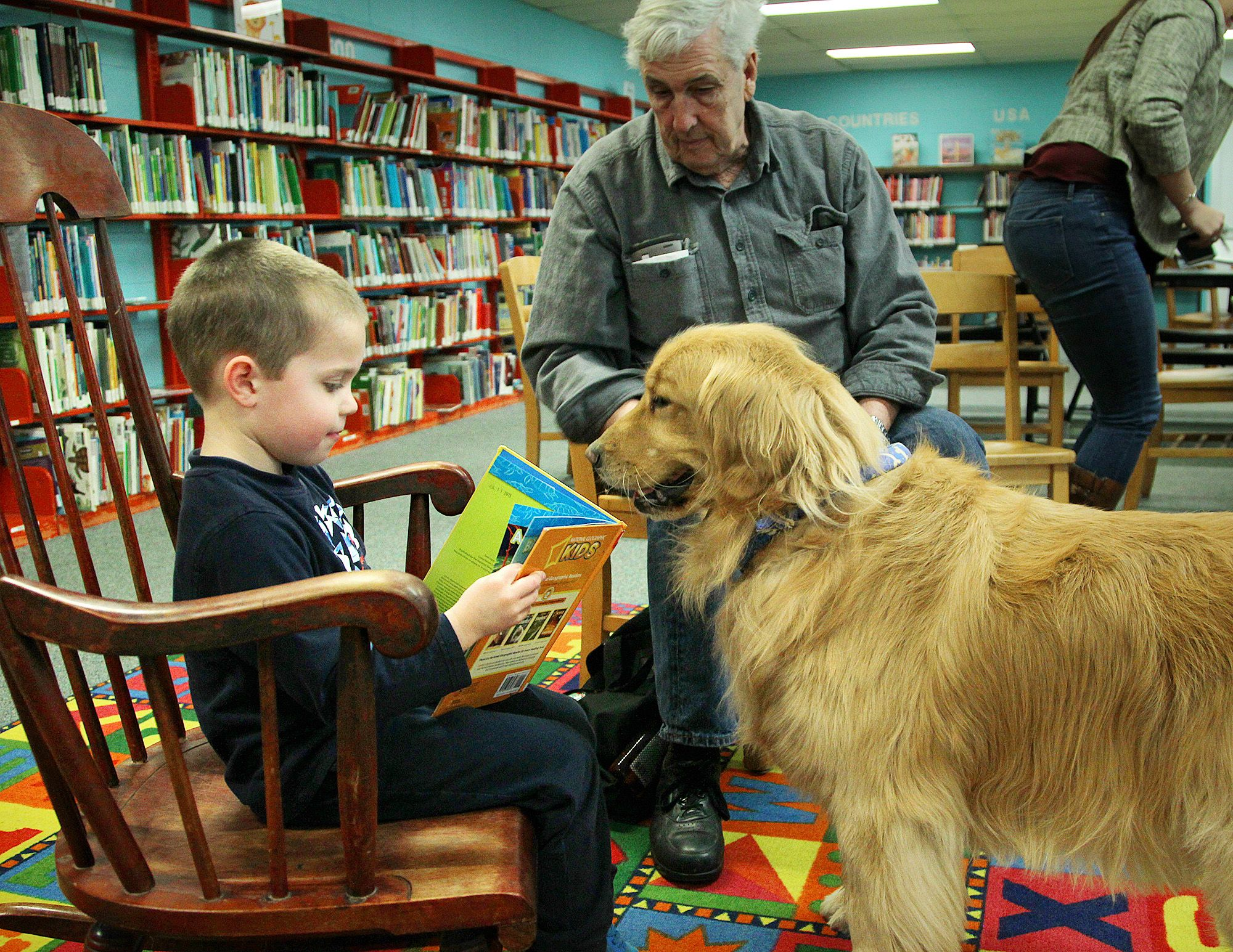 Chase Norkus, 5, of Braintree, reads to Merryl, a golden retriever, belonging to Steve White, of Weymouth who visits the Children's Room of the Tufts Library,Thursday, March 2, 2017.  Gary Higgins/The Patriot Ledger