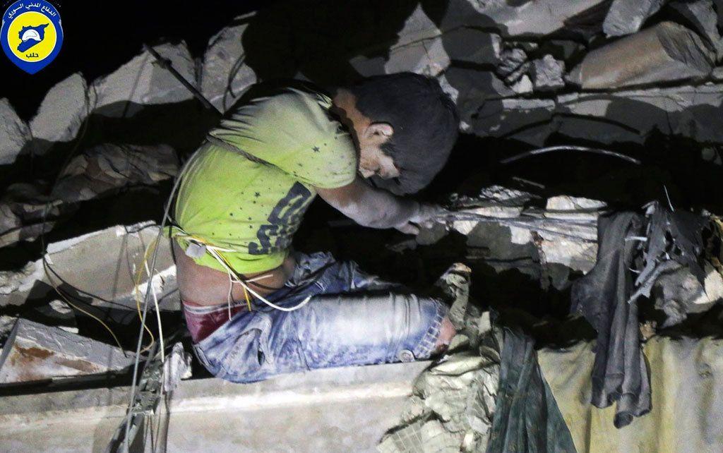 Syyrialaispoika oli jäänyt jumiin pommituksissa sortuneen talon raunioihin Itä-Aleppossa. (AP)