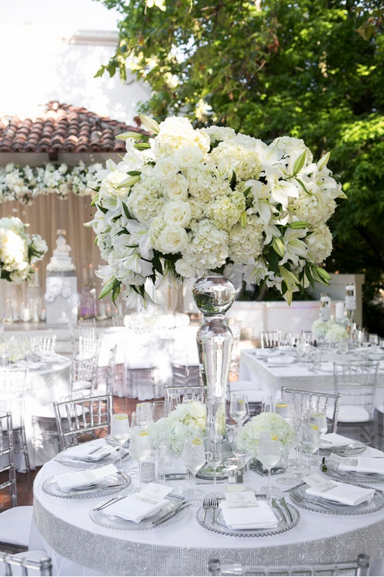 Sparkling, white linens were topped with clear, beaded charger plates and elegant white dinner napkins. A large, clear vase was filled with white and ivory florals, including hydrangea blossoms and lilies. #centerpiece #white #flowerarrangement Photo by: Christine Bentley Photography