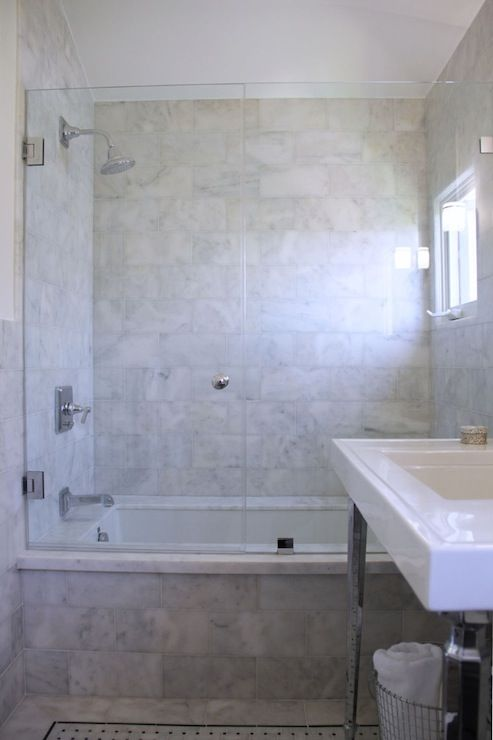 Stunning bathroom with tub shower combo featuring a Carrera Marble ...
