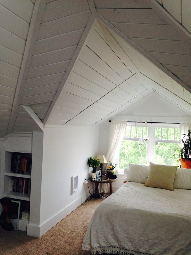 Painted wood ceiling attic bedroom dormer.
