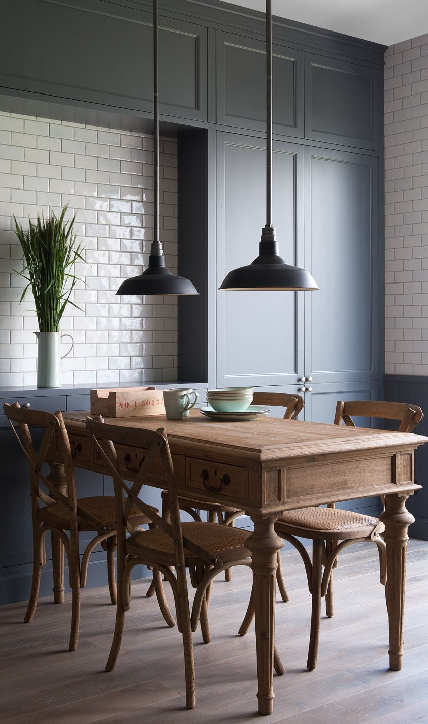 Grey cupboards black pendant lighting brown table and chairs