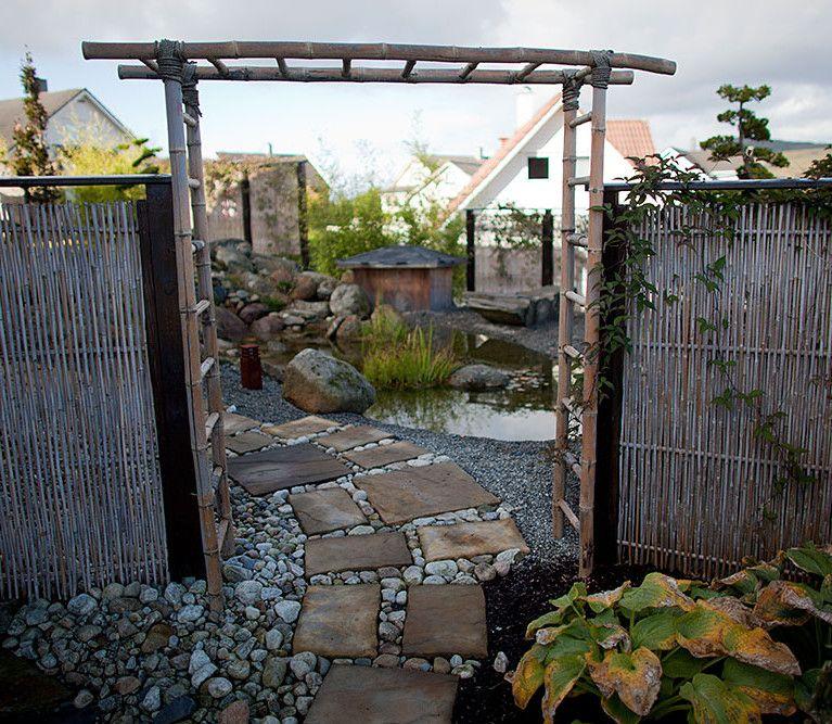 Japansk hage; portal og bambus med klatreplanter og prydgress ved vann ...