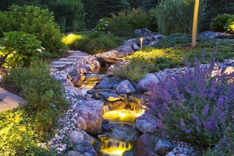 Ein Garten Bachlauf, der wunderhübsch beleuchtet wird Garten - naturlicher bachlauf garten