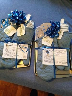two of the prizes for bridal shower games cookie sheet oven mitts and baking accessories complete with ribbon and a handwritten chocolate chip cookie